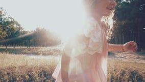 De meisjelooppas langs de weg in het park gelukkig meisje die rond lopen Levendige kleuren stock videobeelden