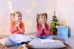 De meisjes in afwachting van Nieuwjaar` s vakantie maken wensen Royalty-vrije Stock Foto's