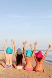 De meisjes in badpakken leunen op het strand achterover Stock Afbeelding