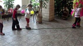 De meisjes besteden het lopen oefeningen aan een kabel in de opleiding van de kinderen` s ruimte stock video