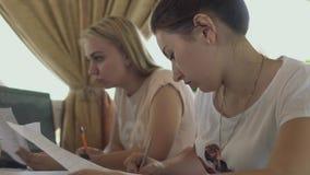 De meisjes bestuderen in koffie stock footage