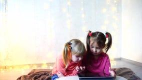 De meisjes betrokken bij gebruik van tablet en zitten op vloer in heldere ruimte met slinger op muur stock footage