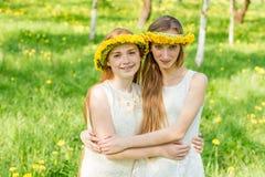 De meisjes bevinden zich met kronen van paardebloemen op hun hea Royalty-vrije Stock Fotografie