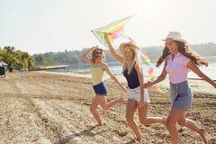 De meisjes bij een partij lopen met een vlieger op het strand royalty-vrije stock afbeeldingen