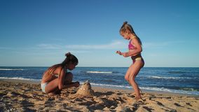 De meisjes bouwen een zandkasteel stock footage