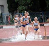 De meisjes concurreren in de Steeplechase van 3.000 Meter Stock Foto