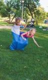 De meisjes concurreren in een relaisras Het springen in zakken Zij lachen en vallen Royalty-vrije Stock Fotografie