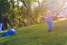 De meisjes concurreren in een relaisras Het springen in zakken Zij lachen en vallen Royalty-vrije Stock Foto's