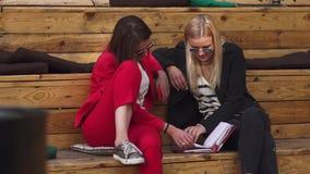 De meisjes controleren notitieboekjezitting bij houten evevation stock videobeelden
