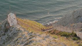 De meisjes daalt de treden aan het overzees Bergen Vrijheid Zonsondergang stock footage