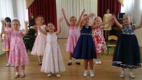 De meisjes dansen en zingen het lied Ochtendprestaties in kleuterschool stock videobeelden
