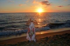 De meisjes in de lange kleding en de zorg bevindt zich door het strand bij sundowne Stock Foto's