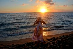 De meisjes in de lange kleding en de zorg bevindt zich door het strand bij sundowne Stock Foto