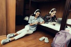 De meisjes die en liggen bekijkend laptop en telefoon zitten royalty-vrije stock foto