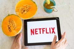 De meisjes die in handen een tablet met Netflix-embleem op de zomer houden dienen met fruit en dranken in Stock Fotografie