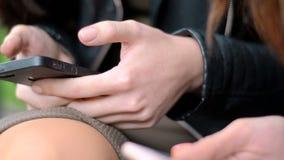 De meisjes die in het Park zitten en houden celtelefoons stock video