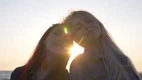 De meisjes die op de achtergrond van de zonsondergang de wind glimlachen slingert hun haar de stralen van de zon tussen hun hoofd stock videobeelden
