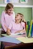 De meisjes die van de school in notitieboekje in klaslokaal schrijven stock foto