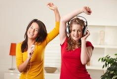De meisjes die van de tiener aan muziek luisteren Stock Afbeelding