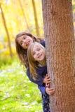 De meisjes die van het de zusterjonge geitje van de herfst in bosboomstam spelen openlucht Stock Foto's