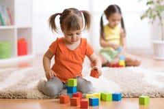 De meisjes die van kinderenpeuters speelgoed thuis, kleuterschool of kinderdagverblijf spelen stock fotografie