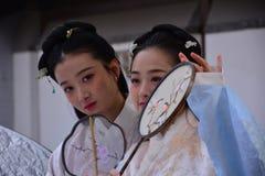 De meisjes die van Peking oude kostuums dragen stock afbeelding