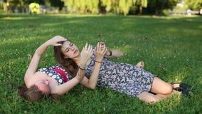 De meisjes die van tienermeisjes op het gazon liggen die beelden van zich op een mobiele telefoon nemen, selfie stock videobeelden