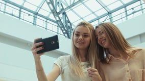 De meisjes doen selfie in vermaakwinkelcentrum stock videobeelden