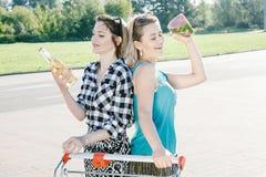 De meisjes drinken alcohol bij de supermarkt royalty-vrije stock afbeeldingen