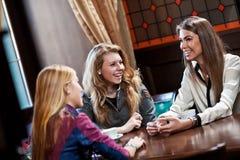 De meisjes drinken koffie in koffiehuis Stock Fotografie