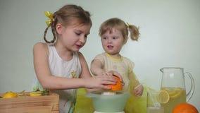 De meisjes drukken sap van sinaasappel stock footage