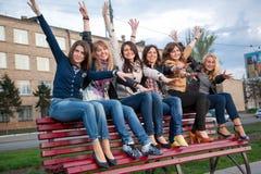 De meisjes in een stad parkeren op een bank stock afbeelding