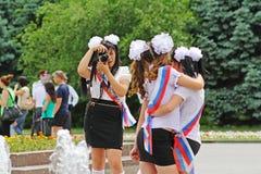 De meisjes in eenvormige school, de bogen en het lint ` Gediplomeerde ` maken een beeld voor geheugen op viering van de Laatste V Royalty-vrije Stock Foto's