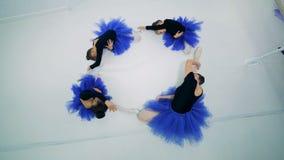 De meisjes en hun balletleraar rekken zich terwijl het zitten uit stock video