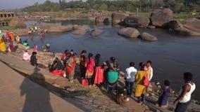 De meisjes gaan naar de kant van de heilige rivier stock videobeelden