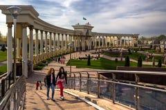 De meisjes gaan over de brug op de achtergrond van de colonnade van het park Stock Foto