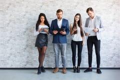 De meisjes gebruiken gadgets, en de kerels kijken in omslagen met documenten Binnen in het bureau Stock Fotografie