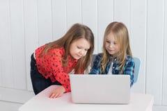 De meisjes gebruiken laptop op de lijst bij ruimte royalty-vrije stock foto