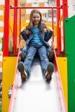 De meisjes glijdt onderaan de heuvel op de speelplaats Royalty-vrije Stock Afbeelding