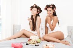 De meisjes in haarkrulspelden zitten op het bed Op een bed is schoonheidsmiddelen en een plaat van fruit Stock Foto