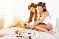 De meisjes in haarkrulspelden zitten op het bed en lezen een luxetijdschrift op glanzend papier Op een bed is schoonheidsmiddelen Royalty-vrije Stock Afbeelding