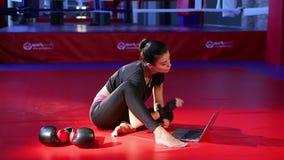 De meisjes kickboxer werken aangaande de computer in de gymnastiek stock videobeelden
