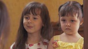 De meisjes kijken in de spiegel Twee zusters lachen bij hun bezinningen Mooie kinderen door de spiegel stock video