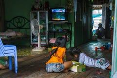 De meisjes kleuren binnen hun huis in een Cambodjaans visserijdorp Stock Foto's