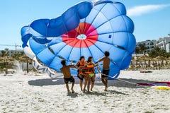 De meisjes komen de hemel op een valscherm van het strand tegen Stock Afbeeldingen