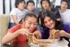 De meisjes kregen de eerste kans om pizza te eten Stock Foto