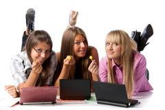 De meisjes leggen met laptops en suikersuikergoed Royalty-vrije Stock Foto's