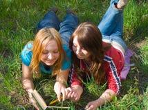 De meisjes lezen het boek. Stock Foto's
