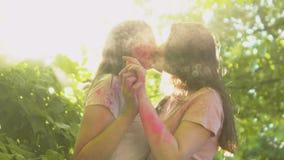 De meisjes in liefde die teder in wolk van gekleurd stof kussen, openen om vrije langzaam-mo te zijn stock footage