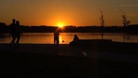 De meisjes lopen langs het strand tegen de zonsondergang hd stock footage